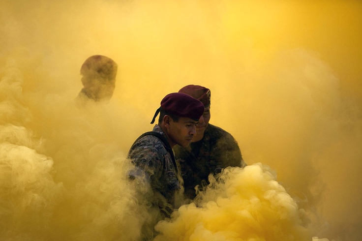 """Members of a special military unit called the """"kaibiles"""" stand amidst smoke from flares during a graduation ceremony in Poptun, Guatemala."""