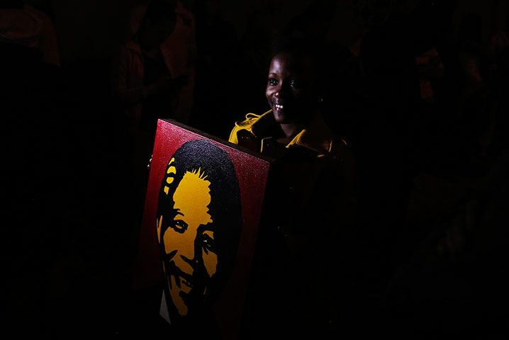 Credit: Siphiwe Sibeko/Reuters A woman outside the house of former president Nelson Mandela in Houghton, Johannesburg, after news of his dea...
