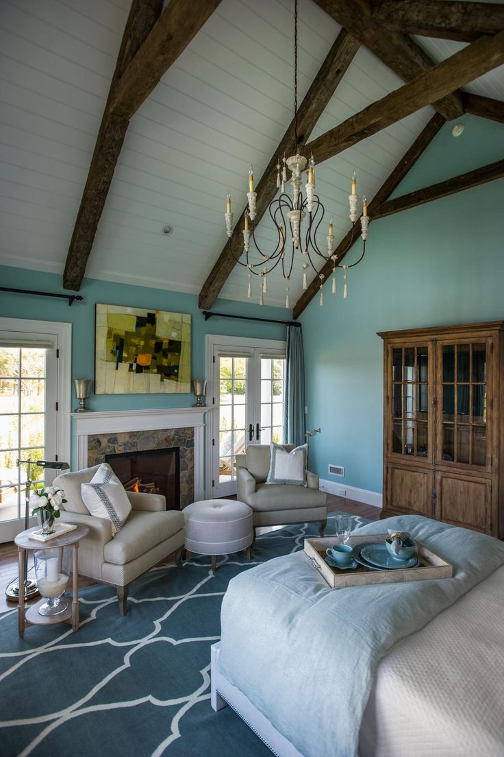 """A vaulted ceiling accented by beadboard and rustic beams draws the eye up and adds a charming cottage feel to the master bedroom. According to Linda, the chandelier is meant to add a feminine touch. She says, """"New England tends to be sort of practical and matter of fact. Everything in here is pretty tailored, and we just wanted to put one little thing in here that was a little bit different – just to have some fun."""""""