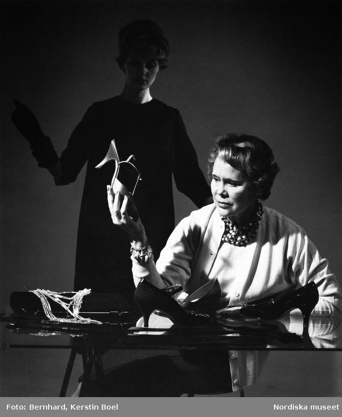 Modeskaparen Aili Pekonen sitter vid ett bord, klädd i ljus kofta, halsband och armband. Håller i ett par höglackade skor med t-slejf. På bordet står tre olika pumps och en handväska. I bakgrunden syns en kvinna i A-linjeformad klänning och långa handskar. Foto: Kerstin Bernhard, 1957