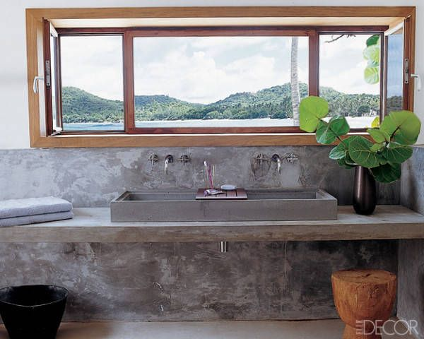 In the master bathroom of a Tristan Auer-deisgned house on the island of Mustique, the cast-concrete counters and sink were brought from France; the Tara sink fittings are by Dornbracht.