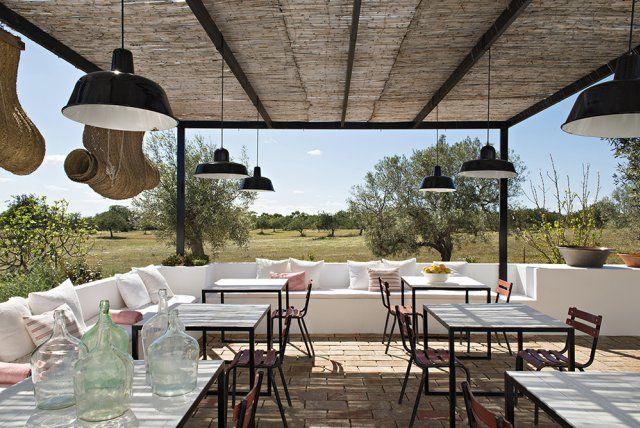 Une terrasse ombragée pour les déjeuners. Vue grand angle sur les champs d'olivier. La terrasse est protégée d soleil par les canisses et des stores coulissants en sparte, une fibre végétale très résistante. Chaises récupérées dans un café de Lisbonne.
