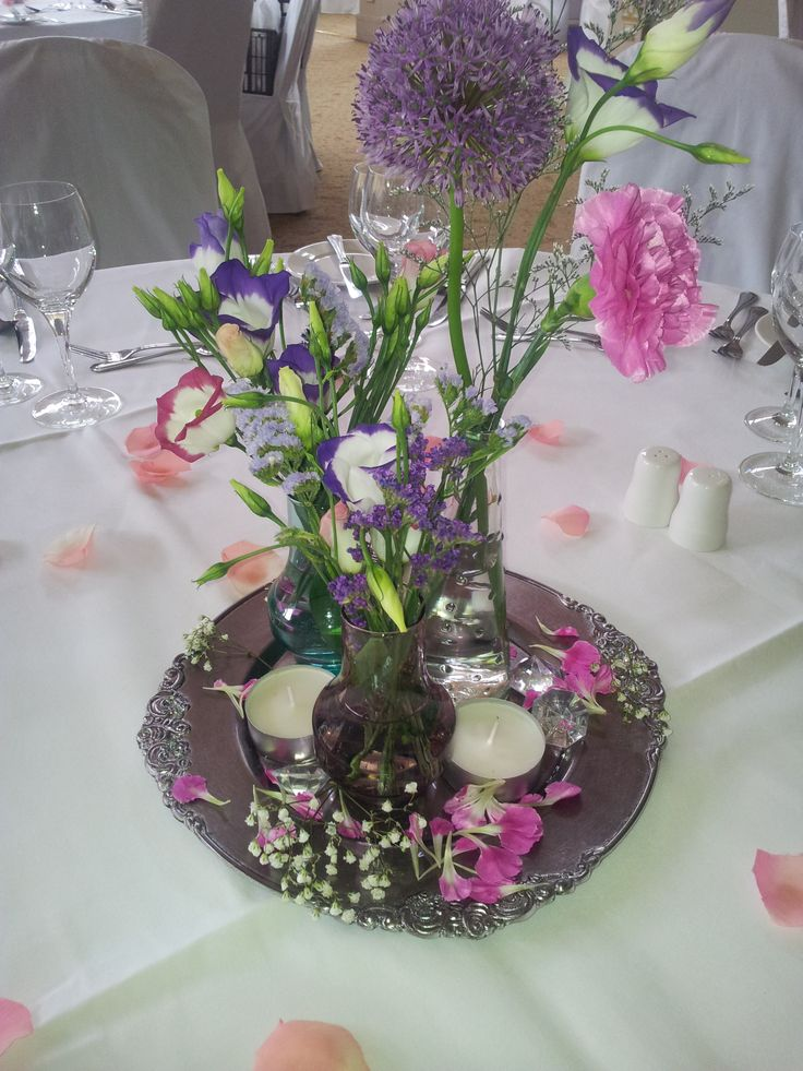 Floral center piece with tea lights on mirror.