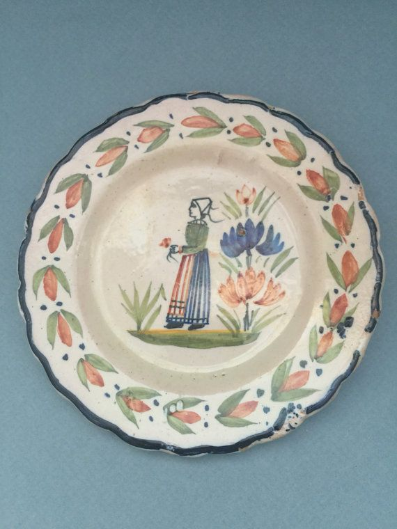 A beautiful antique plate from the well-known Frech pottery Henriot Quimper. It is handpainted and signed at the bottom of the plate.   The plate has a lovely pattern called Le petit Breton, with flowers and a woman in traditional clothes. Looking at the signature, but moreover the pinkish glow of the pottery (visible at the back), the plate can be dated to the 1920's.  The plate measures 14 cm in diameter and has some small chips on the side (see pictures), otherwise the condition is good.
