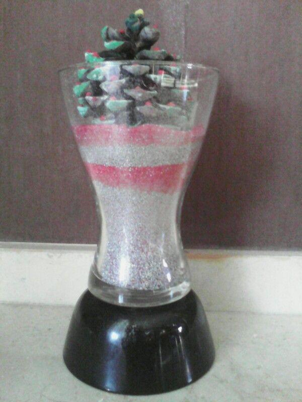 Es un jarrón con arena de colores brillante y una piña decorada
