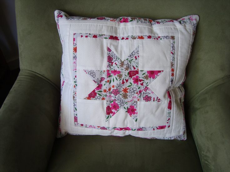 A white cotton cushion cover with a floral patchwork design.