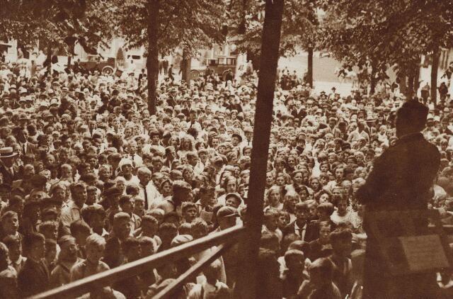 1929. Afbeelding van de aanwezigen tijdens de volkszanguitvoering onder leiding van de heer Goossens, op het Janskerkhof te Utrecht, tijdens de Feestweek.  N.B. De door de gemeente georganiseerde feestweek werd gehouden van 7 t/m 13 augustus en bestond uit o.a. een ruiterfeest op het Suikerterrein, zwemwedstrijden  in de Zweminrichting De Liesbos, verschillende sportwedstrijden en -demonstraties, een volksdansuitvoering, zang- en muziekuitvoeringen en een kermis op drie feestterreinen.