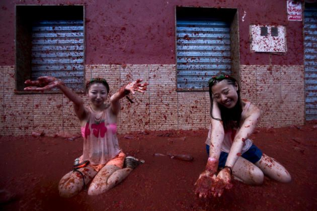 """Revellers take part in the annual """"tomatina"""" festivities in the village of Bunol, near Valencia on August 27, 2014. Some 22,000 revellers hurled 130 tonnes of squashed tomatoes at each other drenching the streets in red in a gigantic Spanish food fight known as the Tomatina."""