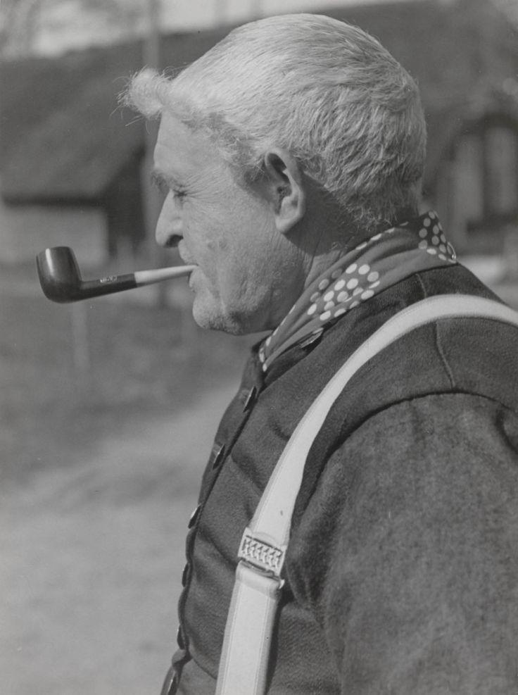 Derk Smit in streekdracht uit Staphorst. Zijn haar is op traditionele wijze gekapt, namelijk rondom het gezicht gekruld. Om zijn hals draagt hij een rode halsdoek met witte motieven. Op het moment dat de foto is gemaakt (1944) werd deze rode halsdoek al bijna niet meer gedragen. De hemdrok wordt gesloten door platte knopen en de broek word opgehouden door bretels. In zijn mond heeft hij een pijp. #Overijssel #Staphorst