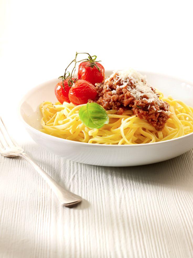 Bereiden: Fruit de ajuin en look in een flinke scheut olijfolie. Doe de gedroogde kruiden en het kruidenboeket erbij. Voeg de tomaten toe en breng op smaak met peper en zout en een snuifje suiker. Laat 30 minuten pruttelen zonder deksel op een zacht vuur. Bak het gehakt rul in een scheutje olijfolie en kruid af met peper en zout. Kook de pasta gaar in licht gezouten water met een scheutje olijfolie. Haal het kruidenboeket uit de tomatensaus en mix de saus fijn. Meng het gehakt onder de…