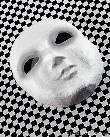Pale gray textured face mask laid obliquely on a black and white checkered board.