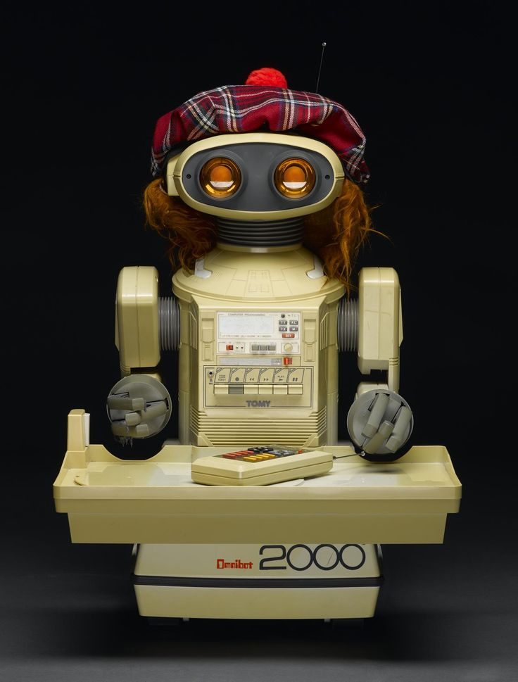 Omnibot 2000 Robot with original box and instruction manual, accessories include carrying tray, 2 remote controls, leather carrying case for remote control, and a costume consisting of a Tartan hat, tartan scarf and a set of fake bagpipes, made by Tomy, Japan, 1984 - 1988