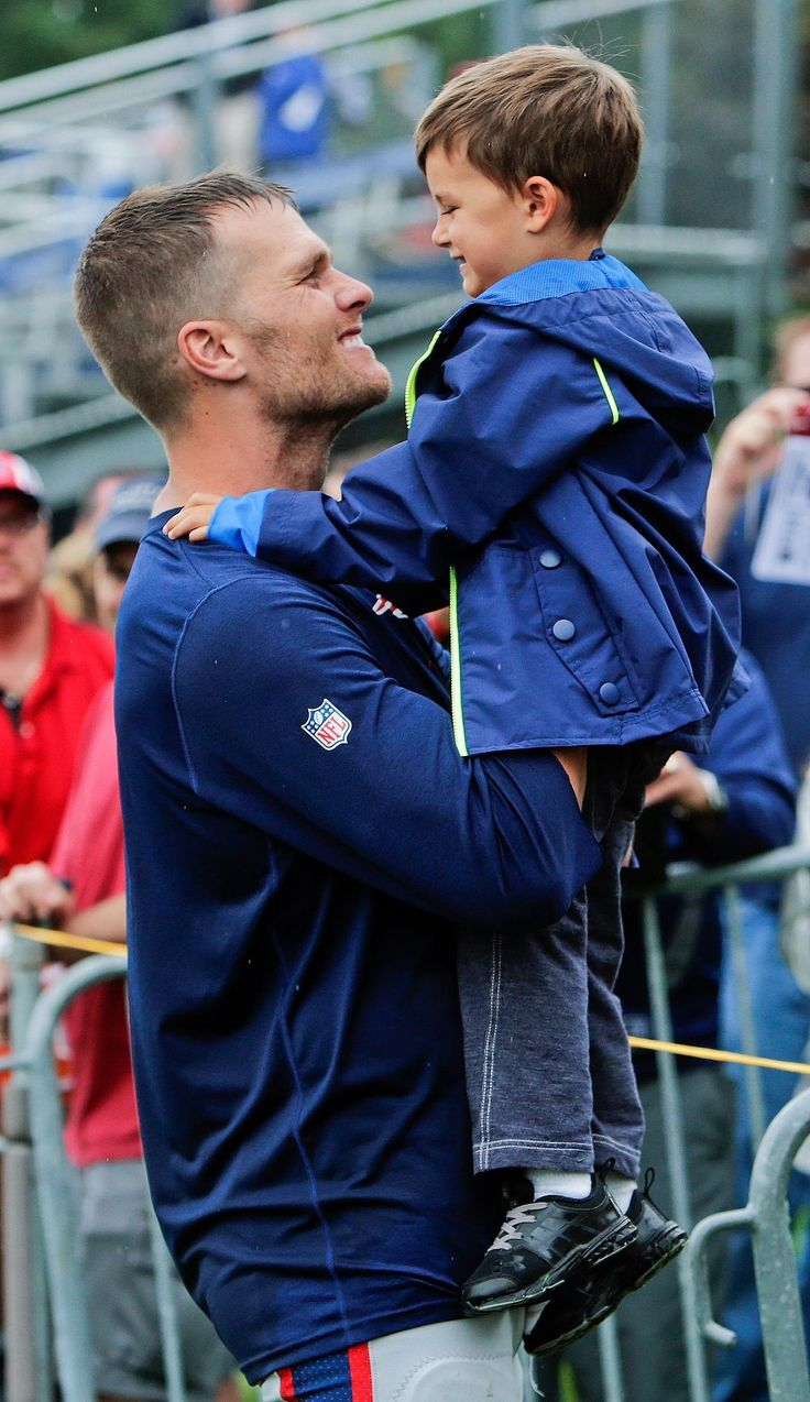 New England Patriots quarterback Tom Brady with his son Benjamin Brady after a joint workout with the Tampa Bay Buccaneers at NFL football training camp, in Foxborough, Mass., Tuesday, Aug. 13, 2013.