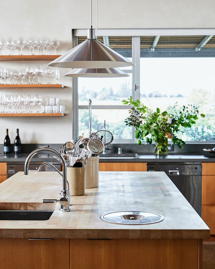 Beyond the central island, two Miele dishwashers flank the main kitchen sink. Outside, deep window overhangs keep the kitchen protected from the hot Sonoma sun.