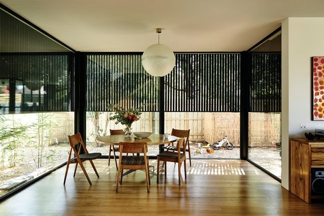 Timber battens extend from the facade over the dining room's glass walls, aiding…