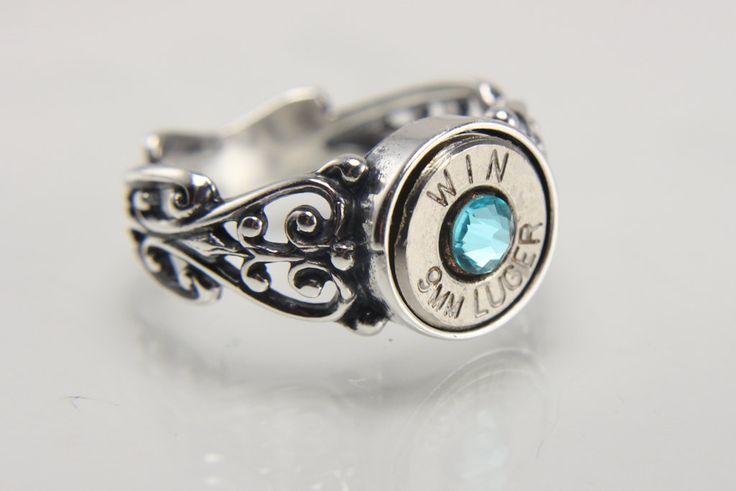 This elegant filigree sterling silver ring features a nickel plated 9mm spent bullet casing that is secured in the rings setting. The sterling silver rings band width measures 4.2mm and the wall height measures 1.6mm. A dazzling Swarovski® crystal is added to the bullet's center and has a diameter of approximately 4 mm. Join my VIP club and get a 10% off coupon: http://eepurl.com/bUPBZv Since real bullets are used manufacturers may vary and bullets may have unique markings on ...