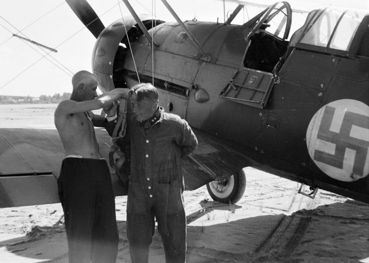 """Finnish technician helps the pilot to """"Gladiator"""" Mk.II fighter put on a parachute"""