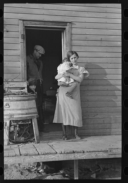 Mrs. Glen Cook and baby with Mr. Cook in background, Little Sioux township, Woodbury County, Iowa