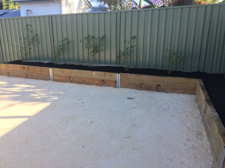Backyard renovation DIY - top outdoor seating area, crushed limestone, wooden sleeper planter boxes, bamboo