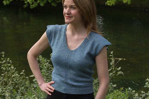 The Kingfisher Tee is a bright, airy knit, designed to wear on a mild summer day letting the breeze blow through the stitches. Fitted to the waist, it is perfect for wearing with a pencil skirt or your favourite high-waisted jeans. A versatile design that sits snug against the waist and loosely over the bust and shoulders. This tee is a seamless simple knit with a modified feather lace pattern running up the centre and around the neckline.