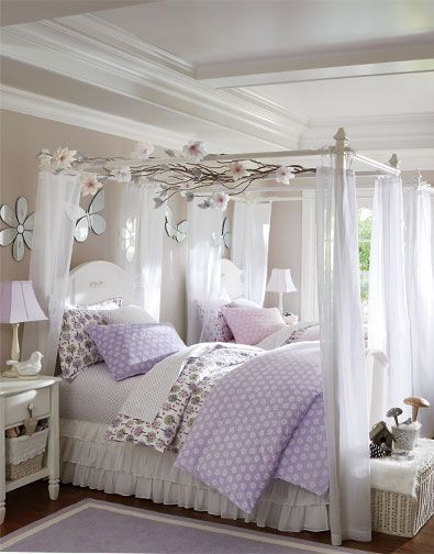 Soft lavender, bright white and a dash of green give this shared room its natural elegance. We've decorated twin canopy beds with branches and silk flowers to evoke visions of a magical forest. Mirrors shaped like butterflies and flowers reflect light and color. A rattan toy chest adds to the room's earthy appeal, while a ruffled bed skirt and sheer canopy curtains give it an open, breezy feel.