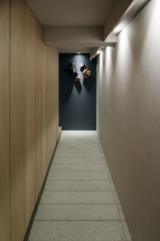 長く延びる玄関土間。床材は大谷石を敷き詰めている。壁面は間接照明のギャラリースペースとシナ合板の扉が連続する大容量の収納。 専門家:青木律典 株式会社デザインライフ設計室が手掛けた、玄関(「ウチソトの間合」-大阪のリノベーション-)の詳細ページ。新築戸建、リフォーム、リノベーションの事例多数、SUVACO(スバコ)