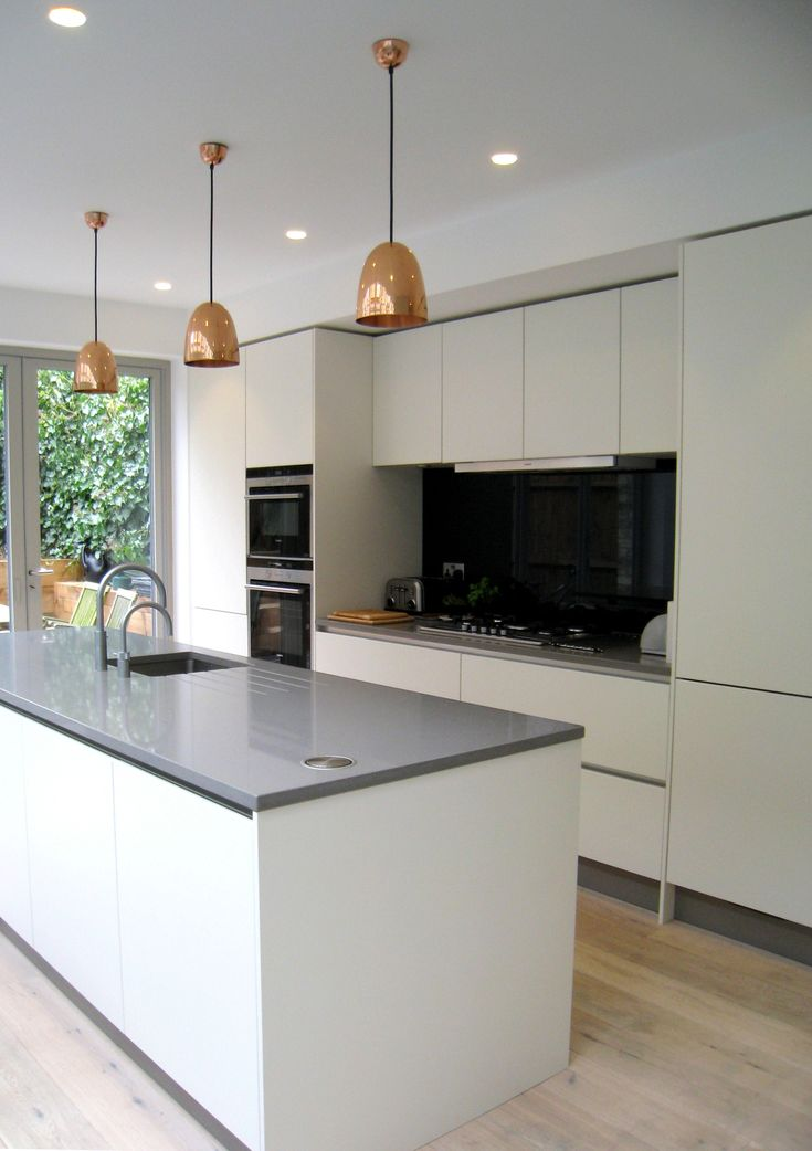 Simple yet stunning white satin lacquer, handless kitchen with Vigo composite worktop and a smart anthracite glass splashback, recently fitted in Crouch End.