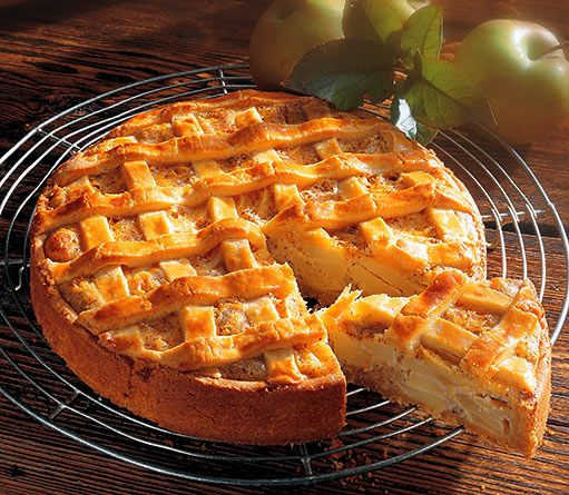 Mřížkový koláč s jablky TĚSTO:      250 g hladké mouky     1/2 lžičky kypřicího prášku     1/2 lžičky soli     150 g másla     2 lžíce medu     2 žloutky  NA PEČENÍ:      kulatou formu (průměr 26 cm)     máslo na vymazání formy     papír na pečení a suchý hrách na zatížení  NÁPLŇ:      6 jablek     1 lžičku citronové šťávy     100 g smetany ke šlehání     2 vejce     3 žloutky     2 lžičky vanilkového cukru     2 lžíce cukru     75 g mletých mandlí