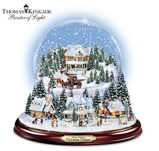 A snow globe made of glass. With snowflakes falling over a cottage or a cute little town! Thomas Kinkade Holiday Illuminated Musical Snow Globe With Victorian Village