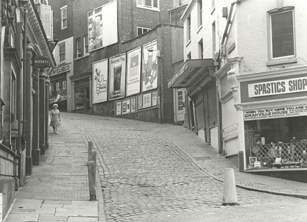 A view of Bridge Street brow with Bennett's Fishmongers to right alongside Spastics Shop (the charity shop for The Spastics Society, today called Scope), Stockport, Greater Manchester, UK, 1970, photograph by C. Warren.