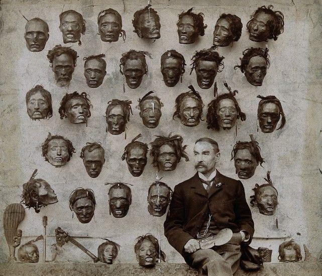 Horatio Gordon Robley posa ao lado de sua coleção de cabeças mumificadas e tatuadas de maoris, também conhecidas como mokomokai.