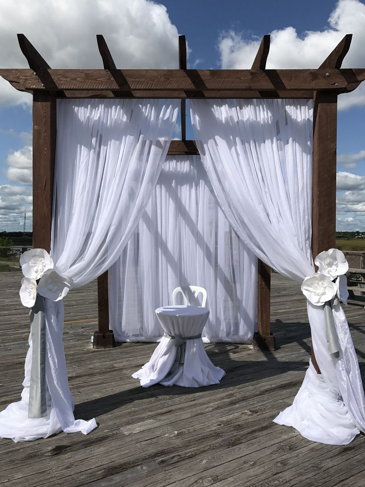 Fabric draped pergola with paper flowers