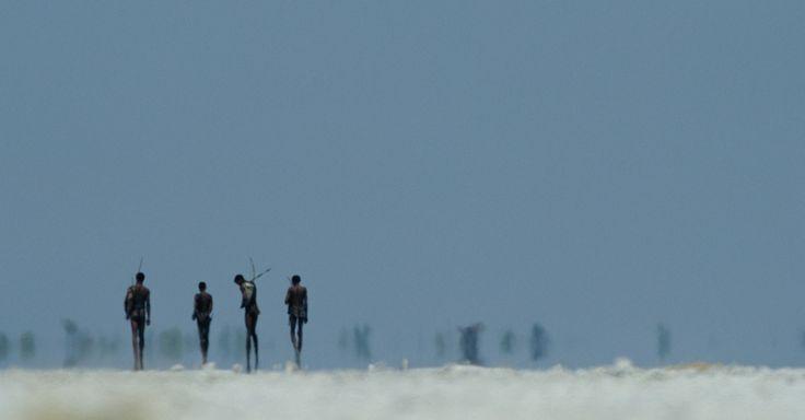 Como numa miragem, bosquímanos usando peles e levando arcos e flechas cruzam uma planície de sal, na reserva de Nyae Nyae, Namíbia. O uso de armas, cães e cavalos é restrito, então eles caçam da maneira tradicional. Vivem em uma vila construída para atrair turistas e geralmente vestem roupas ocidentais