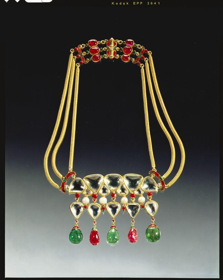 Provenance: Presented to Queen Alexandra by the Maharaja Scindia. Description: Gold necklace;w gold & enamel clasp,w emerald,ruby,pearl & diamond pendant,each w enamel leaf cup mountings on reverse side.Main section joined by cresecent shaped enamel & triple flexible gold cord to clasp of conforming design w rubies. Indian origin.