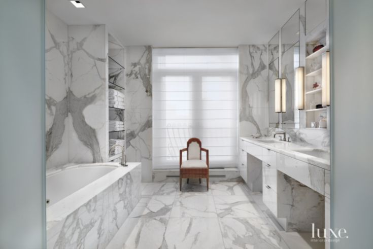 Calacatta gold marble from the stone shop cloaks the master bathroom. A sculptural chair resides near the window, which is adorned with a roman shade. the tub is from waterworks and features a faucet by Kallista.