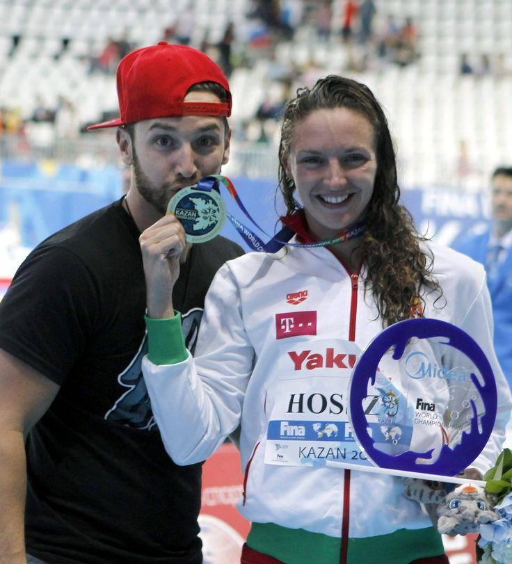 A győztes Hosszú Katinka mutatja aranyérmét a 200 méteres vegyesúszás eredményhirdetése után, mellette férje és edzője, Shane Tusup a kazanyi vizes világbajnokságon 2015. augusztus 3-án. A versenyző világcsúccsal győzött és védte meg címét.