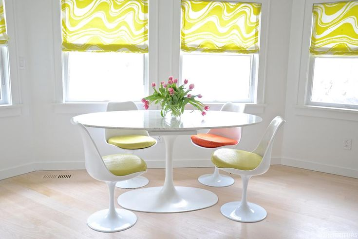 Crisp white pairs with sunny yellow and vibrant orange to create a bright, cheerful atmosphere in this lovely dining nook. The tulip-style dining set and funky Roman shades infuse the space with midcentury modern style.