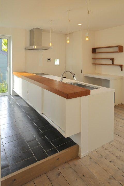 うまく木のカウンターを使ったカフェ風のキッチン。キッチン本体は白でスッキリ。