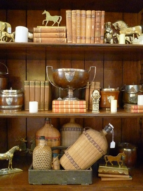 Books, trophies, baskets, and gathered and cherished objects make an interesting bookshelf collection.