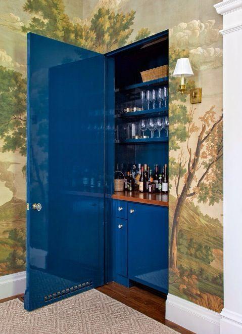 gorgeous wallpaper mural and a chic high gloss blue door concealing a bar
