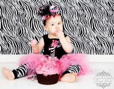 She's #1 Birthday Baby Zebra Tank in Black, White, and Hot Pink      She's the diva of the party! Celebrate her first birthday with this fiercely fun design, or just let everyone know that she's Number One.  This black tank features the number one in zebra print, topped off with a sassy hot pink crown. We know she loves all the frills, so we added a zebra striped satin bow that can be removed for easy washing.