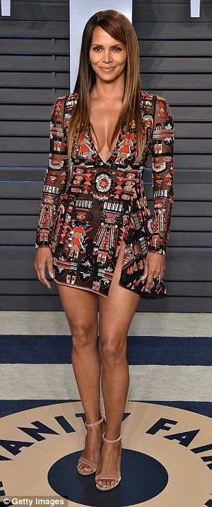 Enviable physique: The dress's black and red Aztec print covered Halle's statuesque physique, but the semi-sheer material did ensure that her taut abs were visible underneath