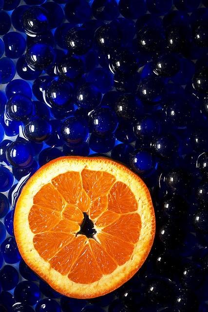 En esta imagen podemos observar dos colores complementarios, el naranja y el azul. El color azul ocupa todo el fondo y su tono se va aclarando ligeramente de izquierda a derecha. El color naranja está colocado en la mitad inferior de la imagen en forma de una rodaja de naranja.