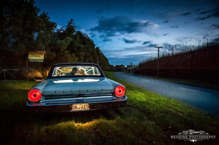 Couple looking romantic in a their wedding car outside Cossars Wineshed. More wedding photography by Anthony Turnham at www.snapweddingphotography.co.nz