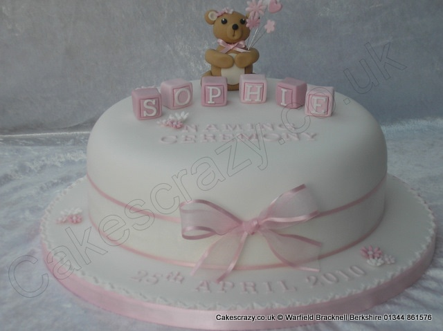 White round naming day ceremony cake with sugar modelled teddy bear and sugar building blocks finished with a pink chiffon ribbon and bow