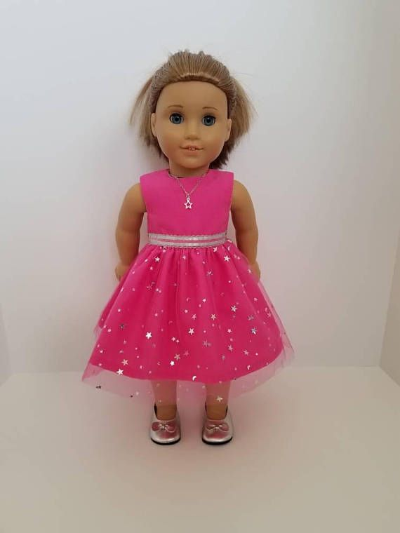 This cute little dress is inspired by the 2018 American Girl Doll of the year, Luciana. It features sparkly stars and moons on pink tulle on a dark pink background. A pretty silver ribbon is sewn around the waist. I have also made an optional silver star necklace. The dress is easy to
