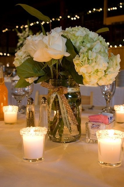 I like the idea of a simple mason jar inspired centerpiece with a few candles surrounding it.