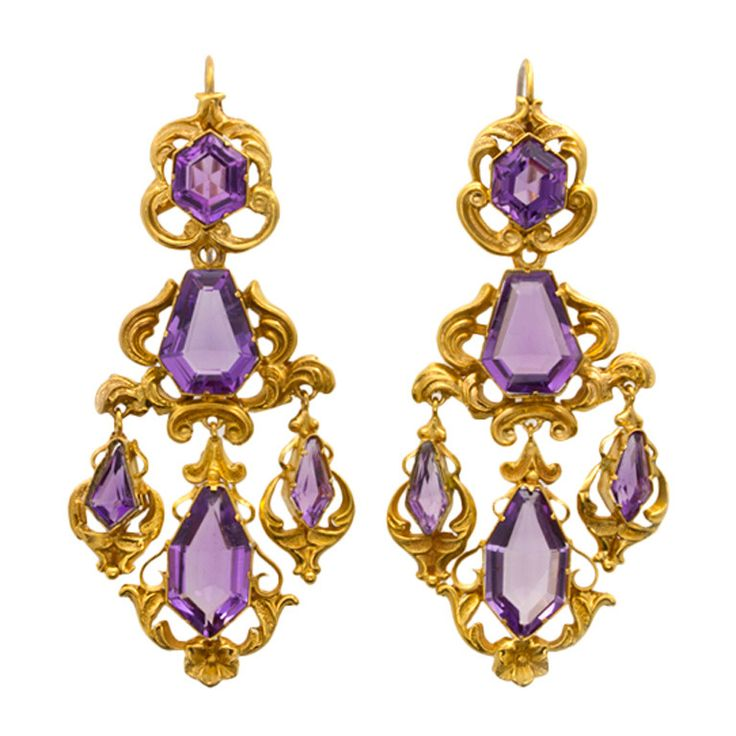 Victorian Amethyst and Gold Drop Earrings. A pair of Victorian amethyst and repousse gold scroll motif earrings, each drop comprising a hexagonal-shaped faceted amethyst to the top, a kite shaped faceted amethyst to the centre with three graduated amethyst drops beneath weighing a total of approximately 25 carats, all rubover-set in ornate yellow gold mount with shepherd hook fittings, gross weight 13.8 grams, circa 1870.