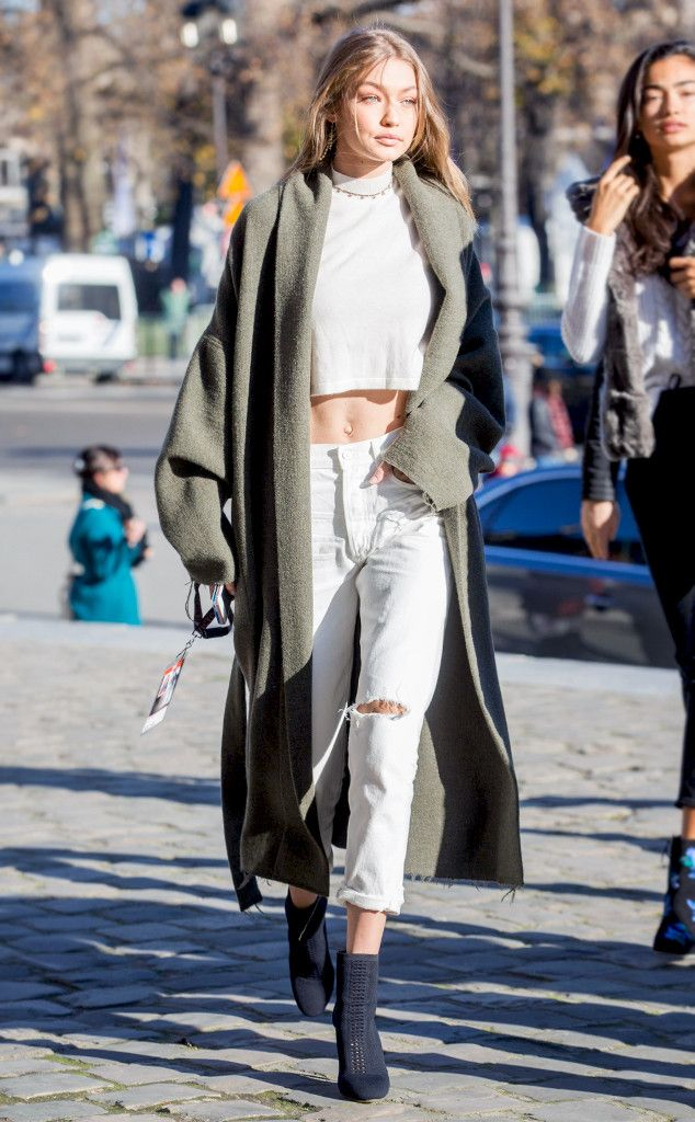 The It Girl model walks the Paris streets in her everyday uniform: a crop top, distressed jeans and oversize coat.