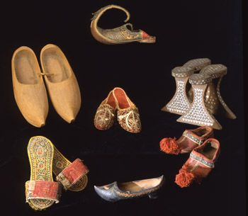 Clockwise from the top: Turkish slipper from Iran, c. 1867; Syrian bathhouse sandals, c. 1900; Syrian child�s shoes, c. 1900; decorated wooden shoe from Spain, c. 1842; sandals from Bosnia, c. 1900; wooden sabots from France, c. 1918; and red velvet slippers with gold embroidery from Syria, c. 1900. (Photo by Hillel Burger)